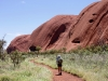 Nirbeeja walks beside the spectacular eastern face of Uluru