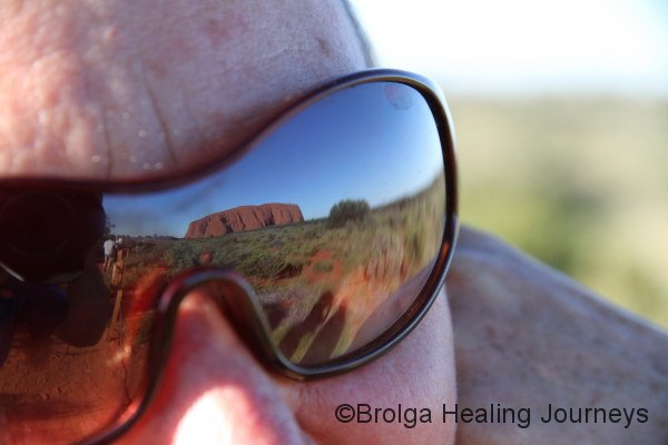 She only has eyes for Uluru.  See the reflection?